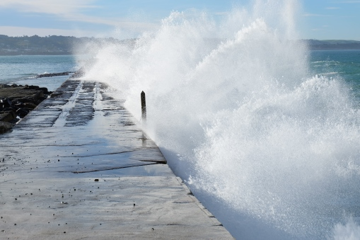 Waves breaking over the breakwater, Oamaru.